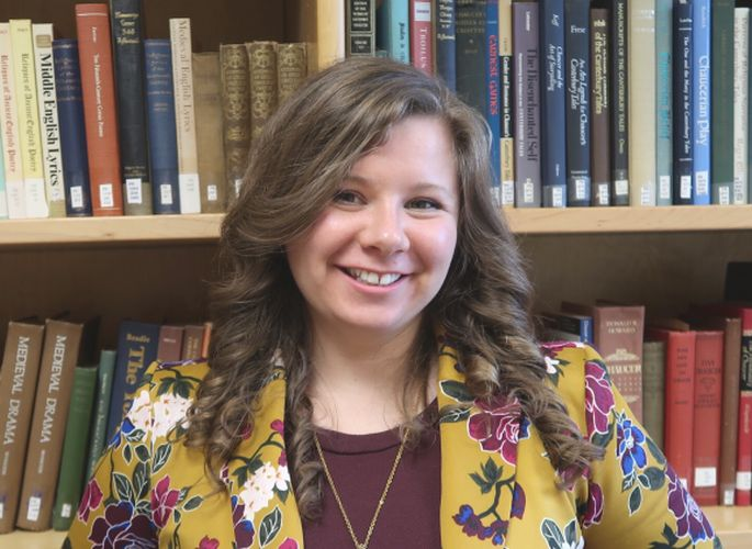Image of Hayley Stefan, body with shoulder-length brown curly hair, wearing a yellow blazer with flowers and a maroon shirt underneath. The figure stands smiling in front of a bookshelf.